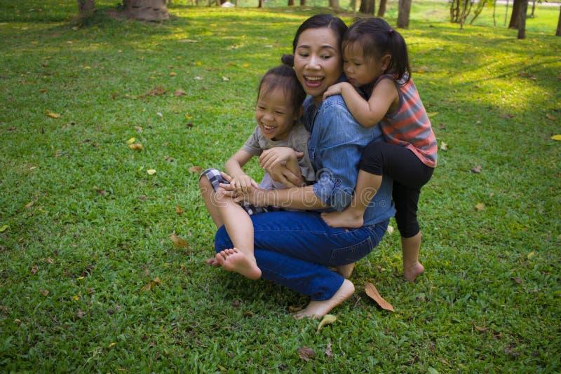 Hijo e hija en felicidad en el exterior en el prado, familia asi?tica divertida de la mam? del retrato de la forma de vida en un  imagen de archivo