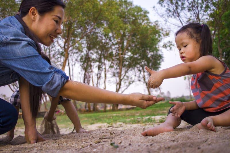 Hijo e hija que juegan con la arena, familia asi?tica divertida de la mam? del retrato de la forma de vida en un parque imágenes de archivo libres de regalías