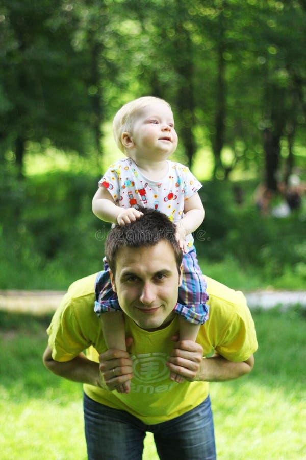 Hijo en los hombros de su padre imagen de archivo