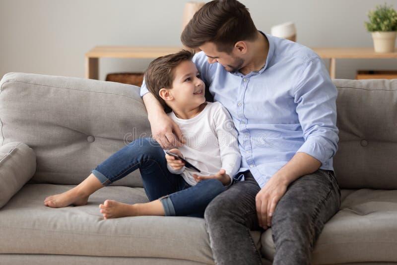 Hijo feliz del pap? y del preescolar relajarse en el sof? junto fotografía de archivo