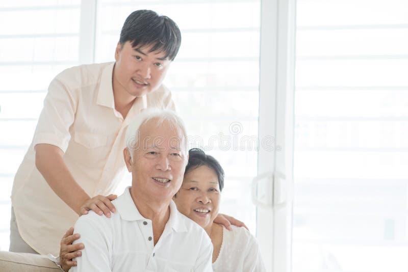 Hijo maduro asiático y viejos padres en casa imagenes de archivo