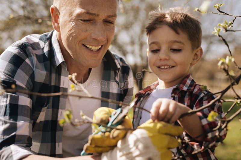Hijo positivo y papá encantados que pasan tiempo en la naturaleza foto de archivo