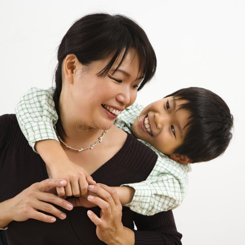 Hijo que abraza a la madre imagenes de archivo