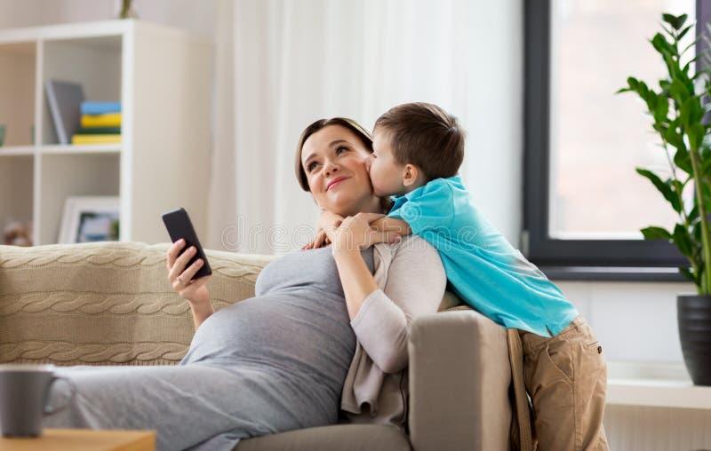 Hijo que besa a la madre embarazada feliz en casa imagen de archivo libre de regalías
