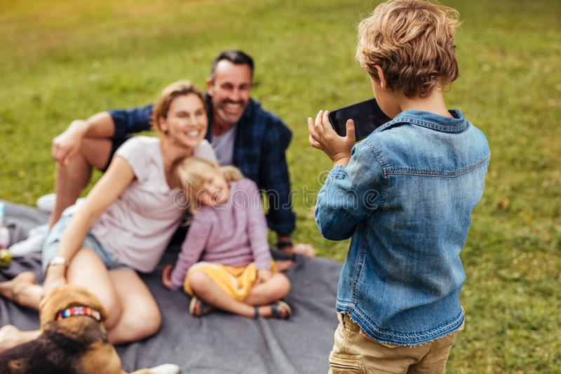 Hijo que fotografía a la familia durante comida campestre en el parque fotografía de archivo