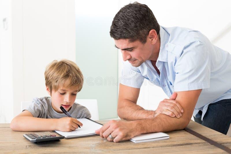 Hijo que hace la preparación mientras que padre que hace una pausa foto de archivo