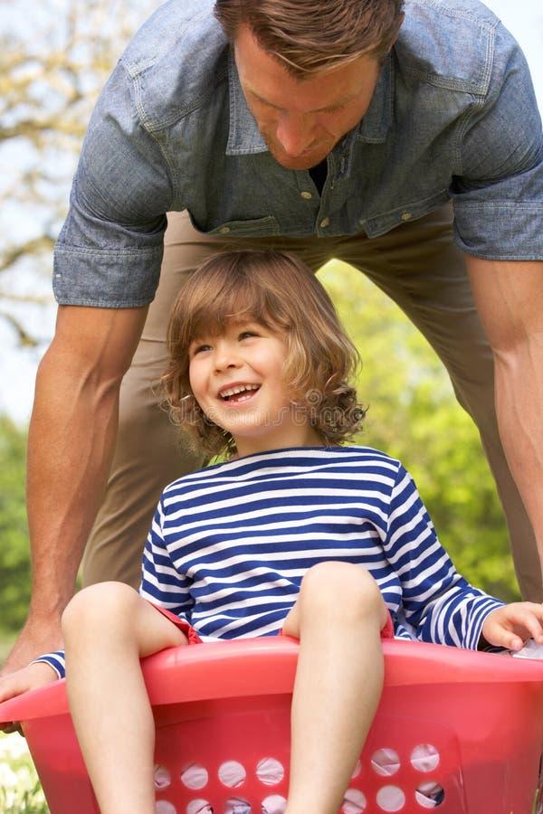Hijo que lleva del padre que se sienta en cesta de lavadero foto de archivo