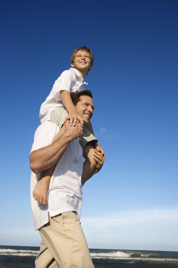 Hijo que lleva del papá fotografía de archivo