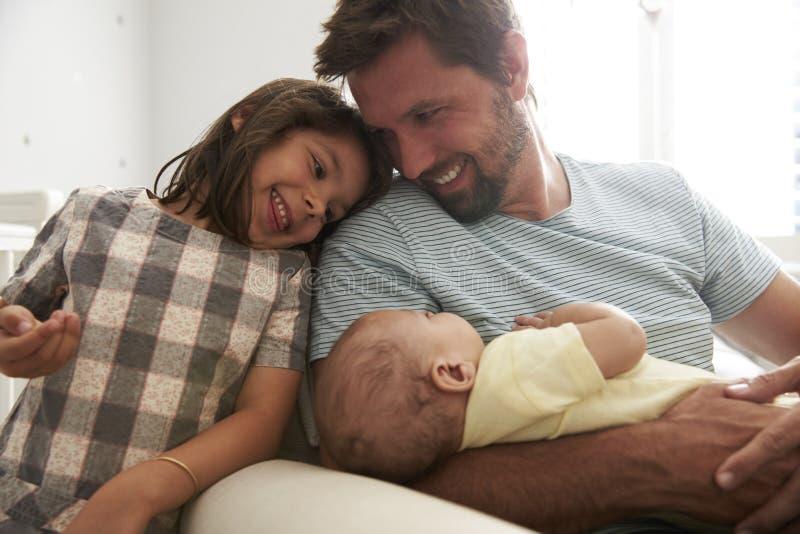 Hijo recién nacido de With Daughter And del padre en cuarto de niños foto de archivo