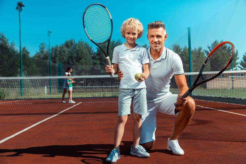 Hijo rizado lindo que siente feliz mientras que juega a tenis con el papá fotos de archivo