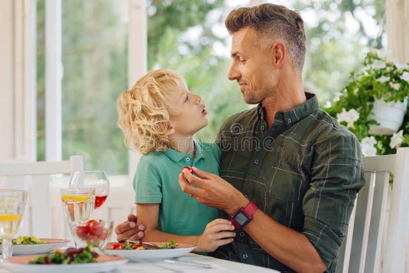 Hijo rubio-cabelludo rizado que habla con el papá mientras que come el almuerzo imágenes de archivo libres de regalías