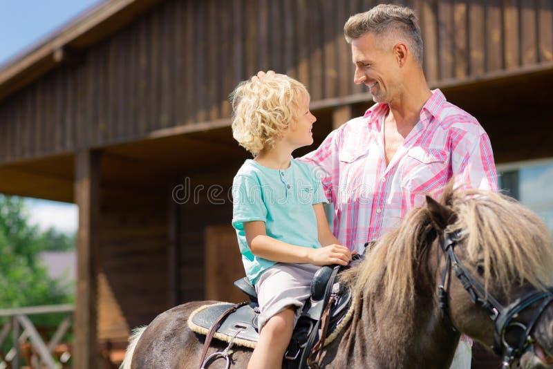 Hijo rubio-cabelludo rizado que se sienta en caballo y que habla con el papá imagen de archivo
