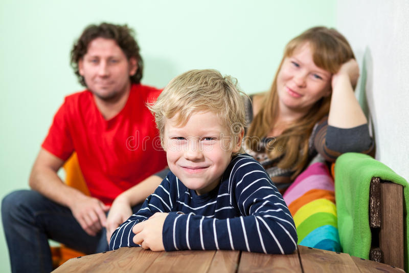 Hijo sonriente del pelo rubio de los jóvenes que se sienta en primero plano de su padre en el sofá fotos de archivo libres de regalías