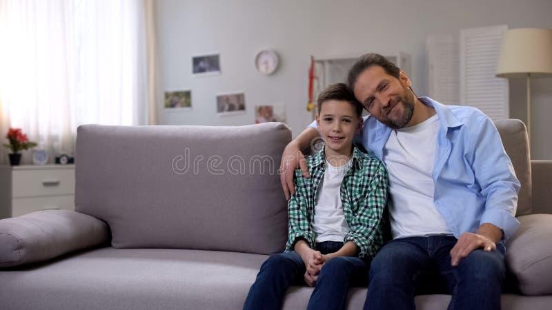 Hijo sonriente feliz del papá y del colegial que se sienta en el sofá, mirando la cámara, familia fotos de archivo libres de regalías