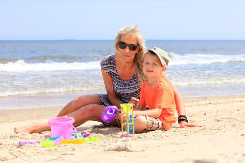 Hijo y madre que juegan los juguetes en la playa fotos de archivo libres de regalías