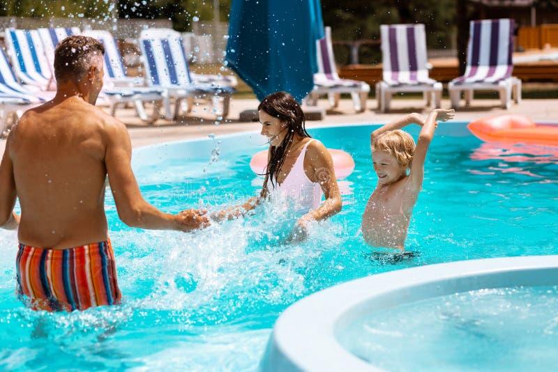 Hijo y padres que salpican el agua mientras que divirtiéndose en piscina imágenes de archivo libres de regalías