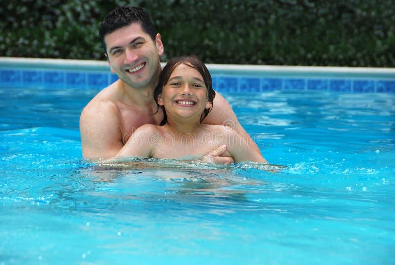 Hijo y papá que gozan de la piscina fotos de archivo libres de regalías