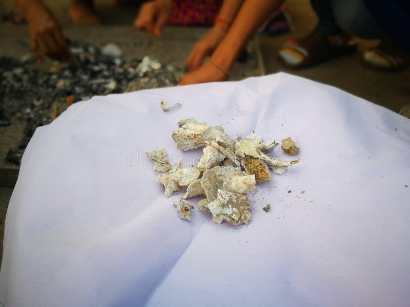 Hijo y parientes del difunto quién recogieron las cenizas por la mañana después de la cremación en el templo fotografía de archivo libre de regalías