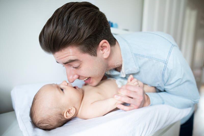 Hijos cambiantes Daiper del bebé del hogar de In Nursery At del padre foto de archivo