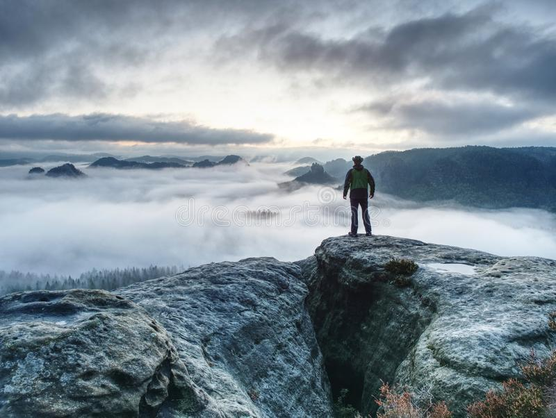Hike in autumn mountains. Man stay above heavy mist in valley. Hike in the autumn mountains. Man stay above heavy mist in deep valley.  Hike in pure nature  is stock image
