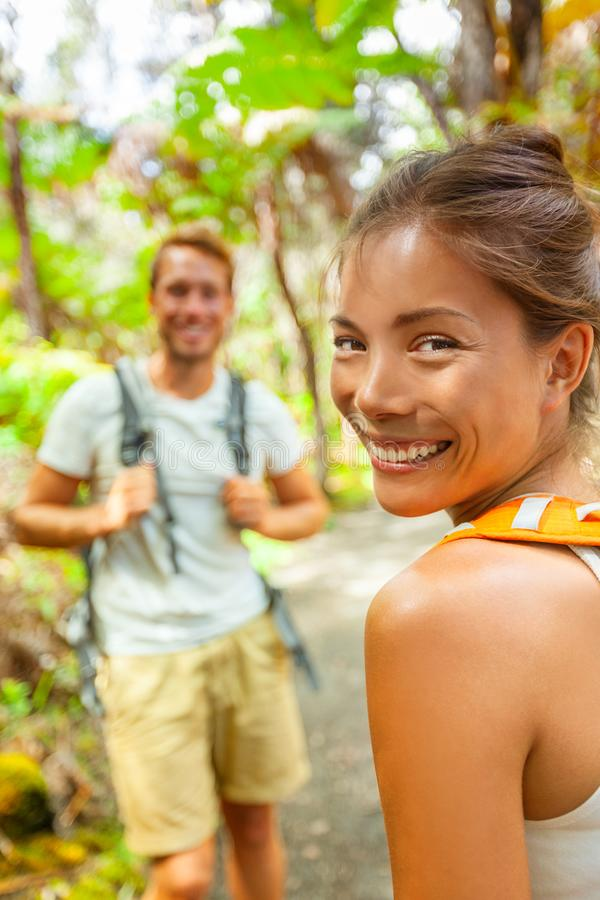 Hike backpackers tourists outdoor travel lifestyle young people walking in forest on trail smiling happy.Two adults couple on royalty free stock images