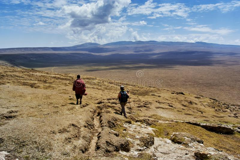 Masai guide hike in the mountains. Hike in Ngorongoro Conservation Area Nationnal park Highlands craters en route for Bulati Village from Nainokanoka with Masai stock photo