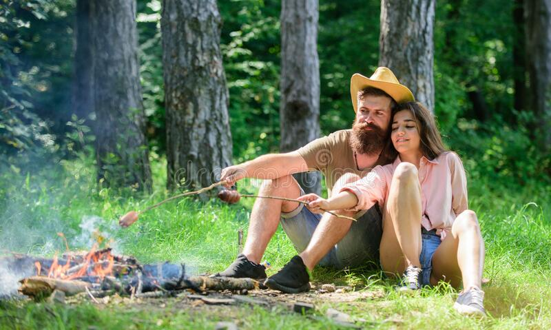 Hike picnic traditional roasted food. Hipster and girl roasting sausages. Couple prepare roasted sausages snack nature. Background. Camping and picnic. Couple royalty free stock photography