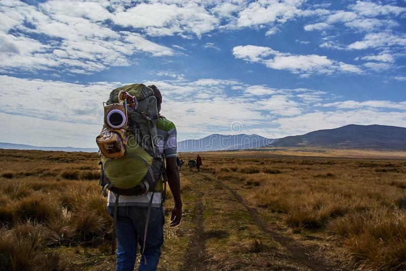 Masai guide hike in the mountains. Hikein Ngorongoro Conservation Area Nationnal park Highlands craters en route for Bulati Village from Nainokanoka with Masai royalty free stock photo