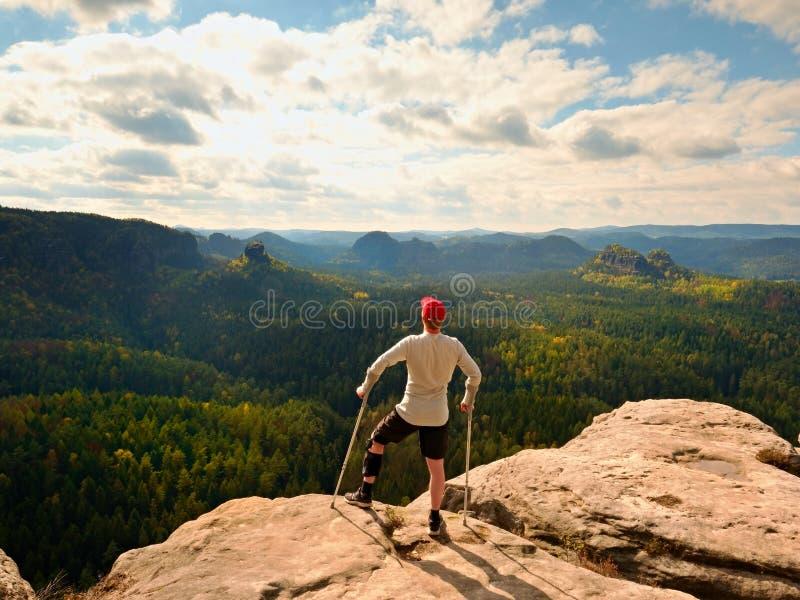 Hiker в серой футболке, костыль медицины и нога исправленные внутри лишают подвижности достиганный горный пик стоковое фото