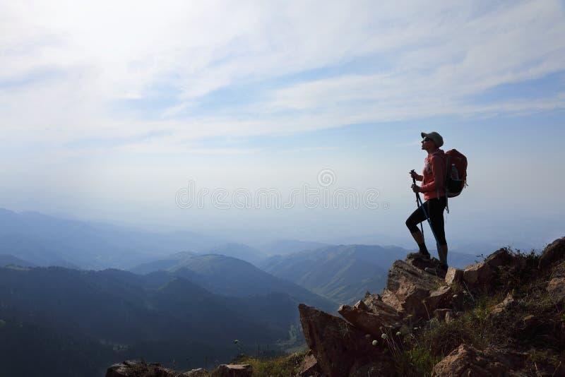 Hiker дамы при рюкзак стоя na górze горы стоковые изображения rf