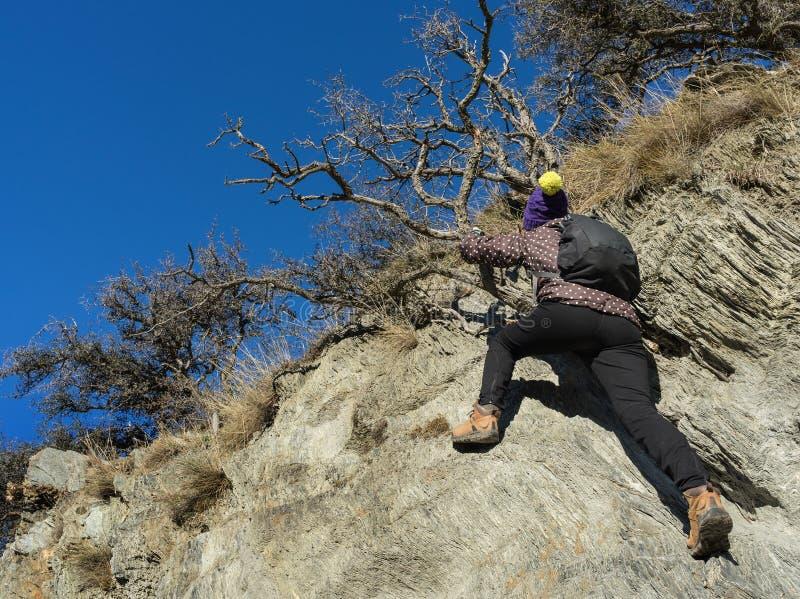 Hiker женщины взбирается утес стоковая фотография rf
