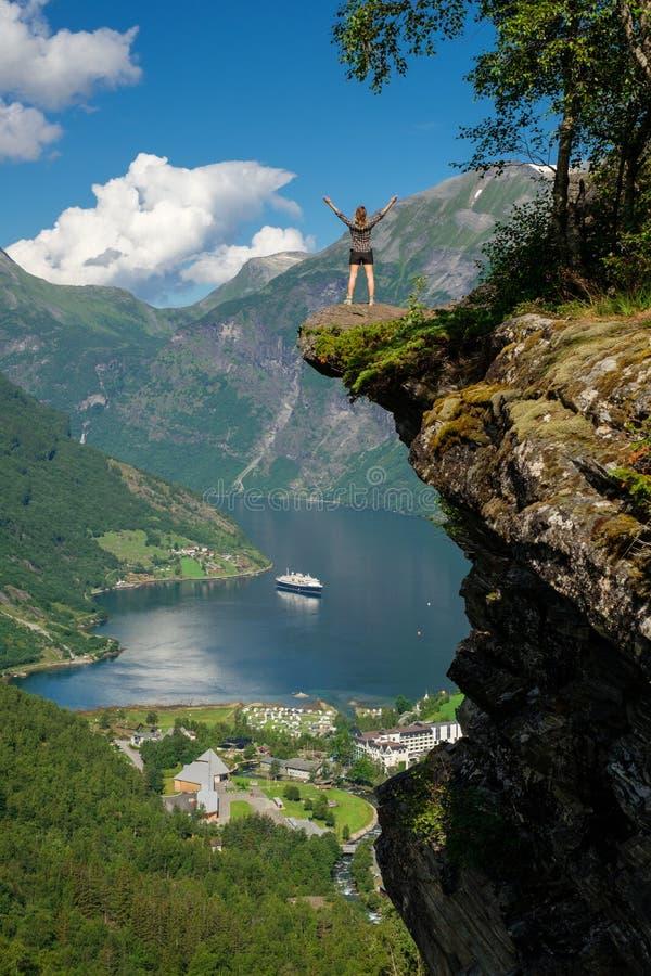 Hiker женщины наслаждаясь сценарными ландшафтами на крае скалы, Geirangerfjord стоковая фотография