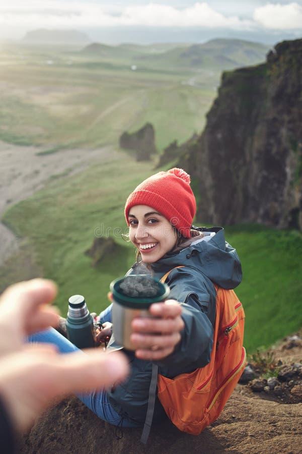 Hiker женщины при рюкзак распологая na górze горы и наслаждаясь заходом солнца в Исландии стоковое фото rf