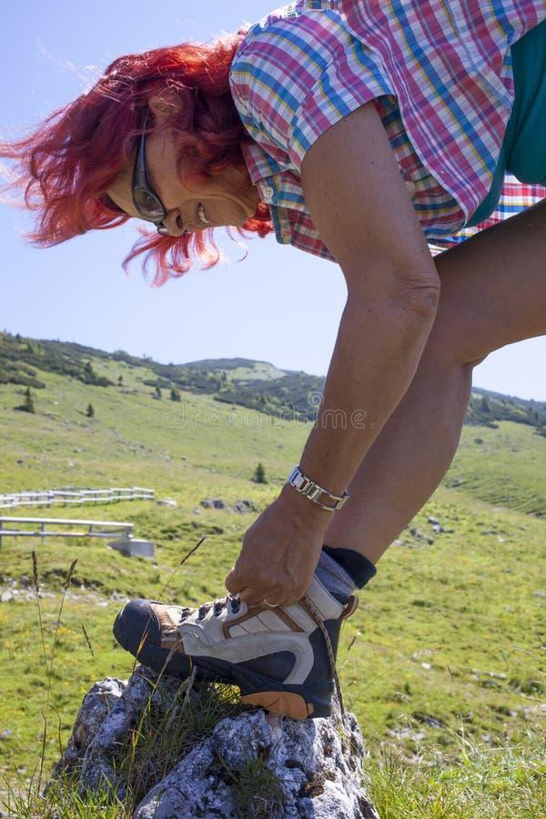 Hiker женщины связывая ботинок шнурует, высоко в горах стоковое изображение rf
