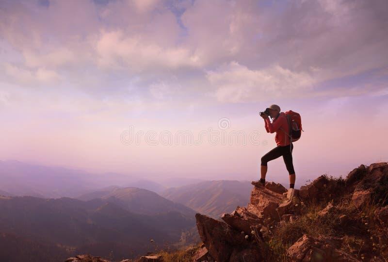 Hiker молодой женщины принимая фото на горном пике стоковая фотография