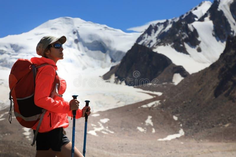 Hiker молодой женщины с рюкзаком в горах стоковые фотографии rf