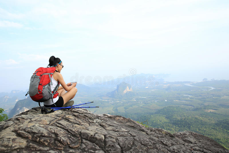 Hiker молодой женщины принимая фото с умным телефоном стоковые фото