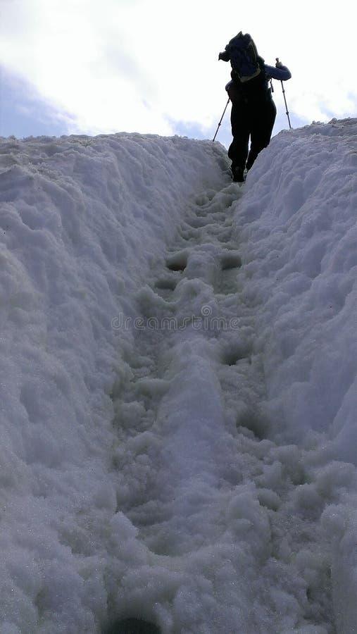 Hiker достигая верхнюю часть снежного холодного пика с рюкзаком стоковое фото rf
