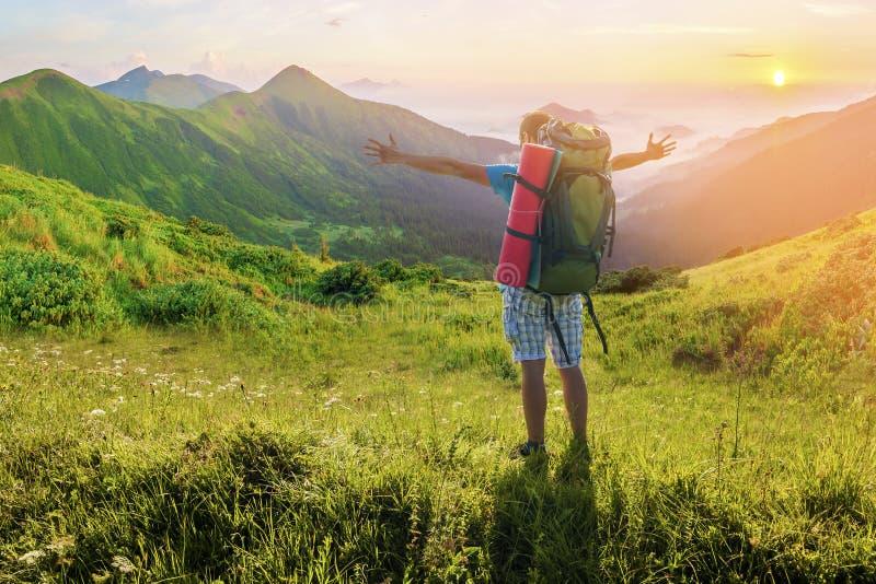 Hiker при рюкзак стоя в горах Изумительная земля природы стоковые изображения rf