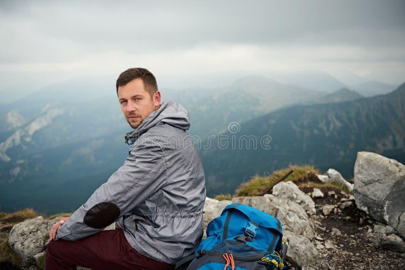 Hiker сидя на пике с горами в расстоянии стоковые изображения rf