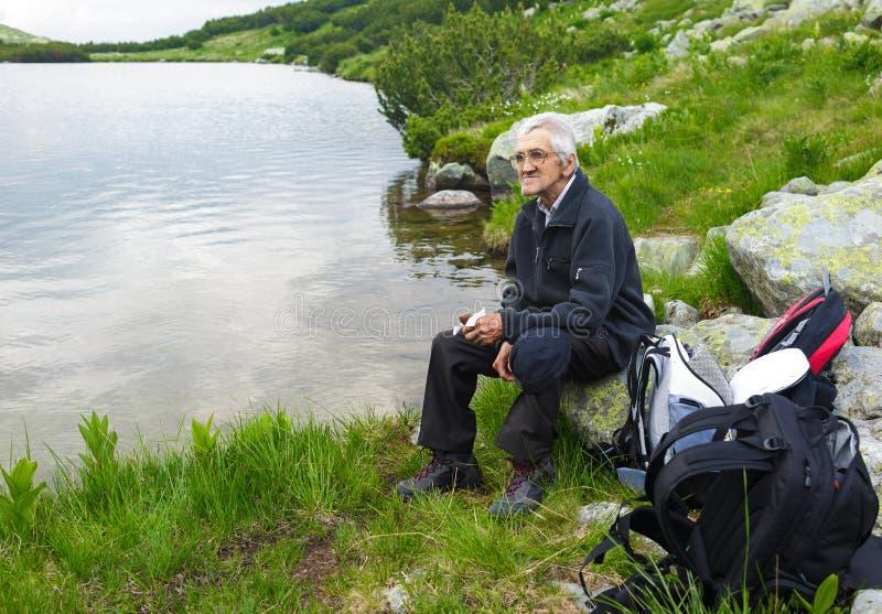 Hiker старшего человека имея пролом стоковое изображение