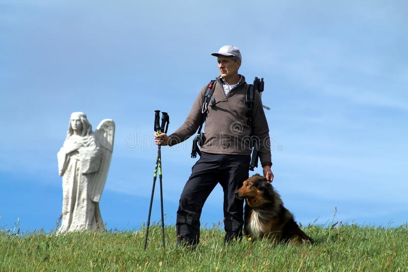 Hiker стоя на верхней части холма с его собакой стоковые изображения rf