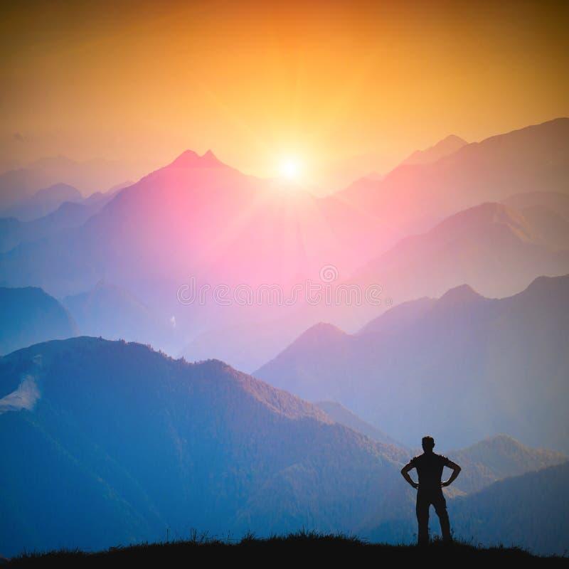 Download Hiker стоя на холме и наслаждается цветами восхода солнца Стоковое Фото - изображение насчитывающей выносливость, hiking: 106940492