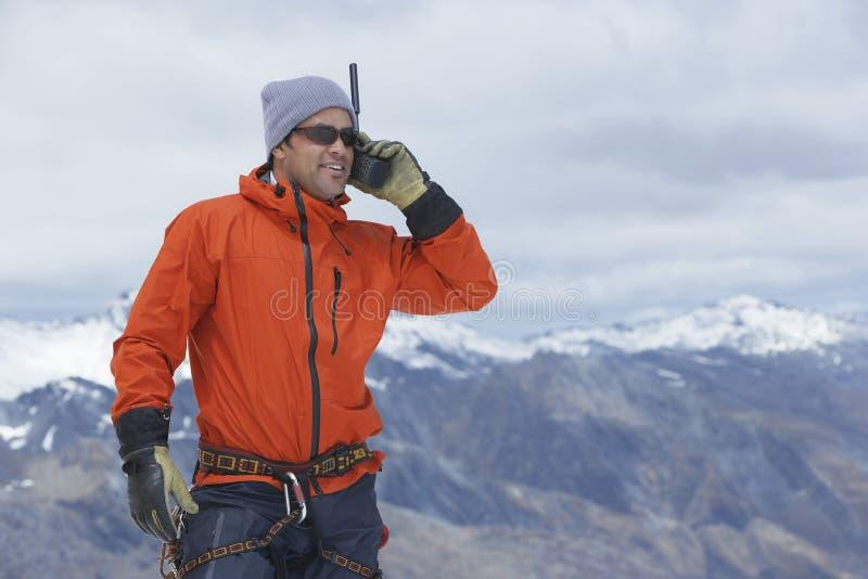 Hiker с звуковым кино Walkie против горного пика стоковая фотография