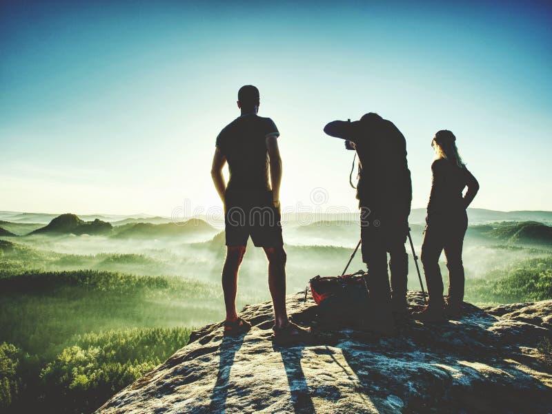 Hiker с 2 фотографами на восходе солнца дозора саммита на горизонте стоковые изображения rf