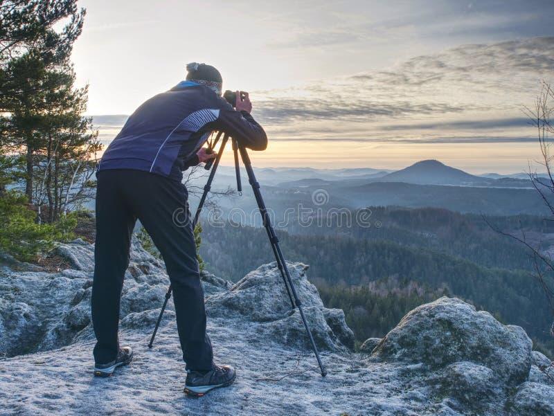 Hiker admiring stunning misty mountain range, sunny morning stock photo