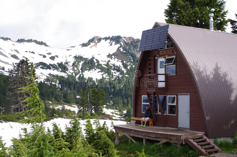 Hiker and an alpine hut stock images