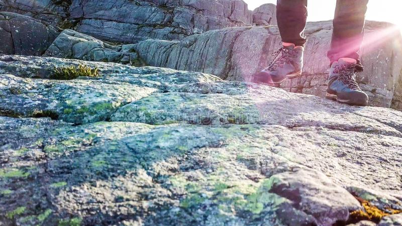 A hiker is aproaching the camera, only his hiking boots are visible. A close up on a male hiking boots. The man is walking front. Soft sunrise beams are stock images