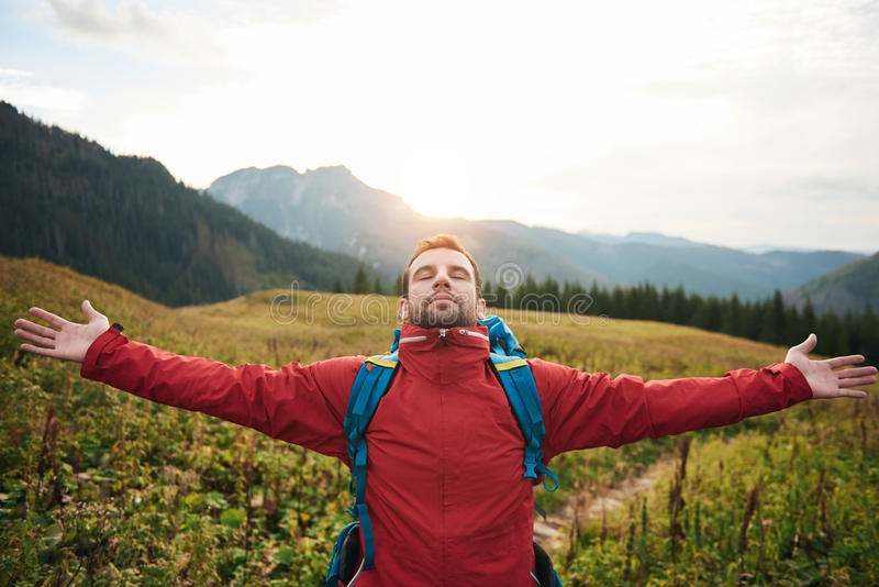Hiker with arms raised to the sky embracing dawn. Young man in hiking gear with his arms raised to the sky embracing the sunrise while trekking in the wilderness stock images