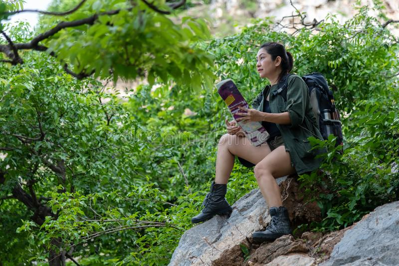 Hiker asia woman look binoculars and standing on mountain.  Female adventure backpack and camping on hike in outdoor nature. royalty free stock photography